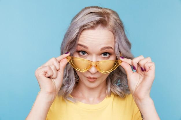Retrato de surpresa linda garota posando de câmera e segurando óculos amarelos em pé na parede azul.