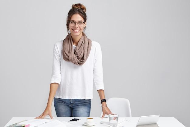 Retrato de talentosa freelancer feminina, trabalha remotamente, usa tecnologias modernas