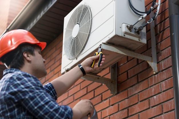 Retrato de técnico em capacete conectando unidade de ar condicionado externa