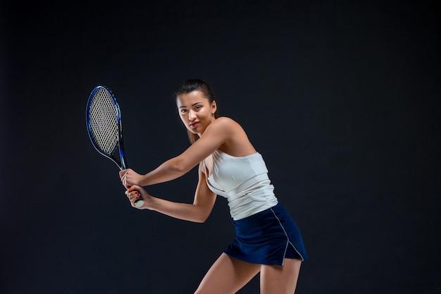 Retrato de tenista linda garota com uma raquete na parede escura