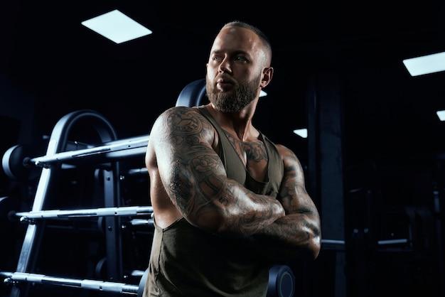 Retrato de tenso fisiculturista masculino em roupas esportivas, apoiando-se no carrinho.