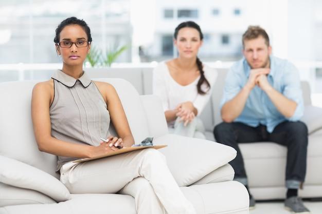 Retrato de terapeuta e casal infeliz