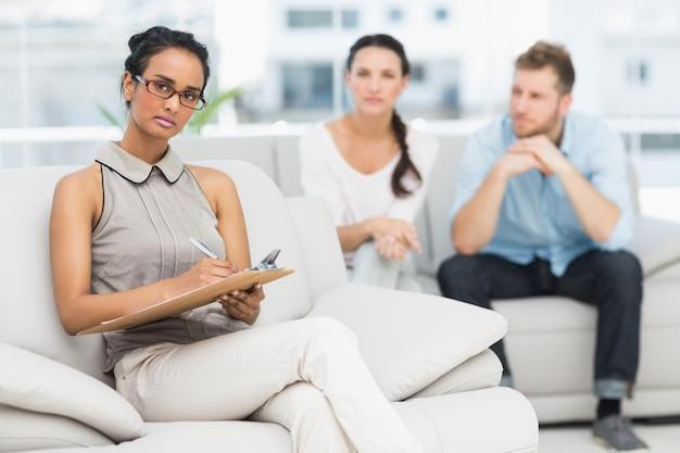Retrato de terapeuta sério e casal infeliz