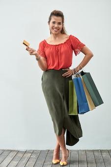 Retrato de tiro completo da mulher feliz com sacos de compras, segurando um cartão de crédito ao ar livre