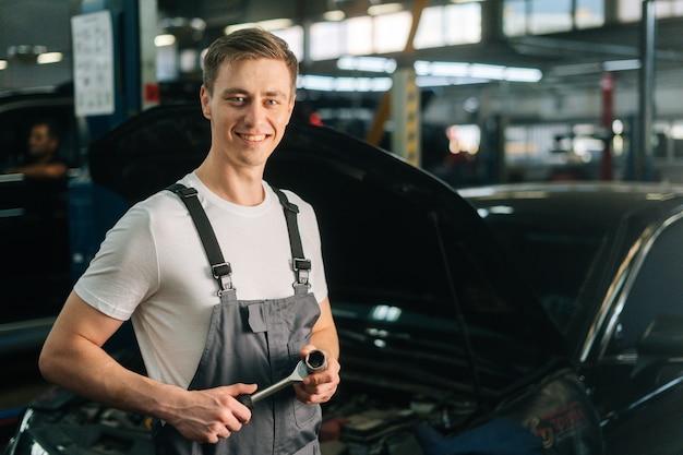 Retrato de tiro médio de alegre bonito jovem mecânico vestindo uniforme, segurando ra chave especial.