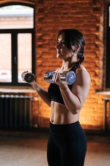 Retrato de tiro médio de jovem atlética com belo corpo forte em roupas esportivas, exercícios com halteres durante o treinamento. treino feminino de fitness caucasiano fora exercitando-se no ginásio escuro.