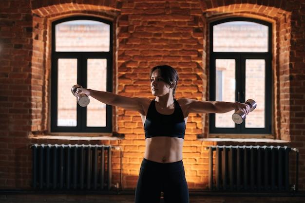 Retrato de tiro médio de jovem atlética com belo corpo forte, vestindo roupas esportivas segurando halteres nos braços retraídos. treino feminino de fitness caucasiano fora exercitando-se no ginásio escuro.