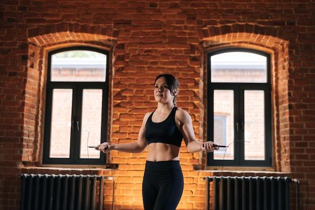 Retrato de tiro médio de jovem mulher atlética de aptidão com corpo bonito e forte em roupas esportivas, exercitando-se com pular corda durante o treinamento. treino muscular caucasiano feminino no ginásio escuro.