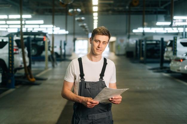 Retrato de tiro médio de sorriso bonito jovem mecânico masculino vestindo uniforme, segurando o suporte da prancheta.