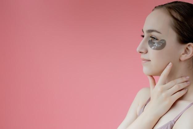 Retrato de tiro na cabeça perto sorridente jovem com máscara de adesivos hidratantes sob os olhos, olhando para a câmera, apreciando o procedimento de cuidados com a pele.