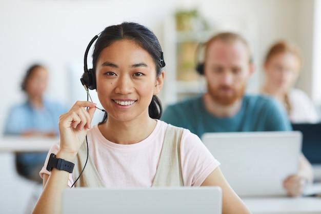 Retrato de trabalhador asiático do serviço ao cliente em fones de ouvido, sorrindo durante o trabalho