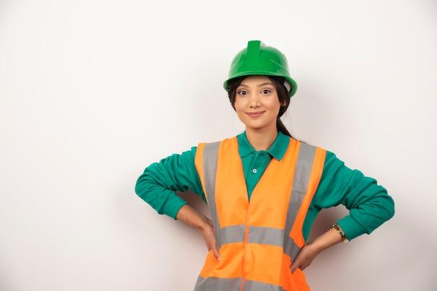 Retrato de trabalhador da construção civil feminino em fundo branco.