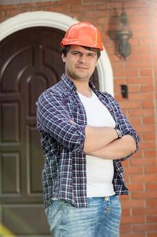Retrato de trabalhador da construção civil sorridente com as mãos postas posando contra a porta da casa nova