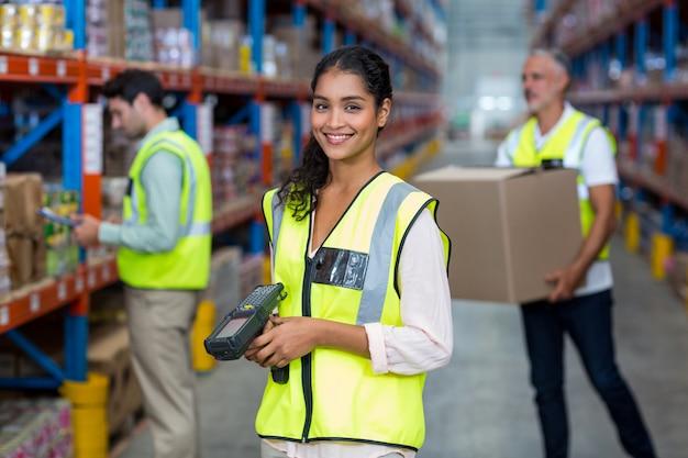 Retrato de trabalhador de armazém feminino em pé com o scanner de código de barras