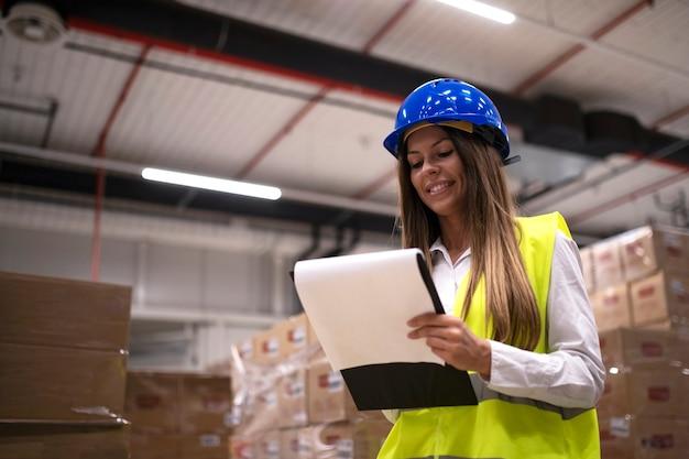 Retrato de trabalhador de armazém feminino verificando mercadorias e pacotes no departamento de armazenamento.