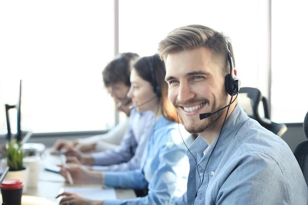 Retrato de trabalhador de call center acompanhado por sua equipe. operador de suporte ao cliente sorridente no trabalho.