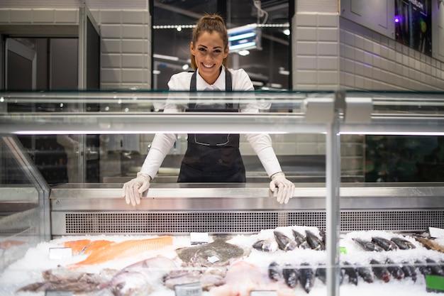 Retrato de trabalhador de delicatessen de supermercado com peixe congelado no gelo pronto para a venda