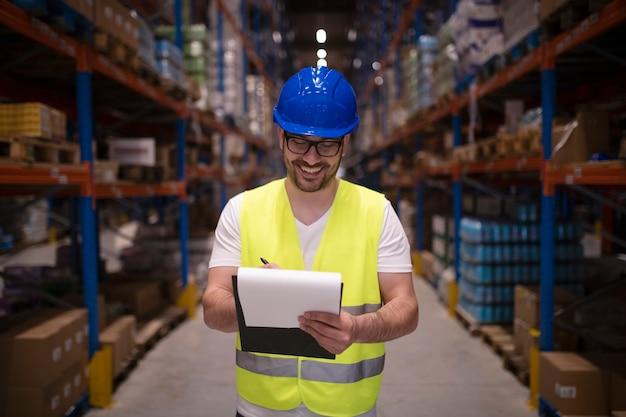 Retrato de trabalhador de depósito em uniforme de proteção verificando mercadorias para distribuição ao mercado