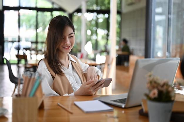 Retrato de trabalhador de escritório feminino assistindo vídeo no celular no escritório.