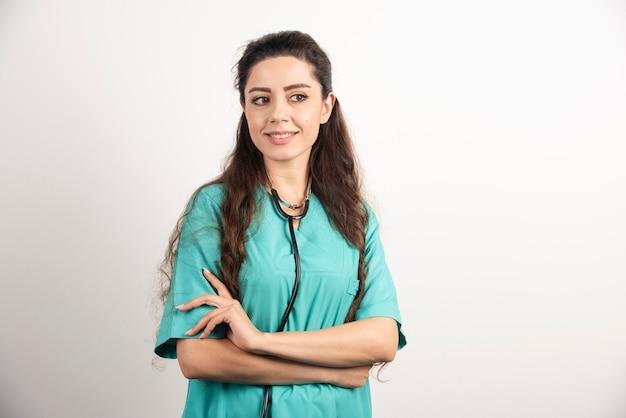 Retrato de trabalhador de saúde feminino posando com as mãos cruzadas.