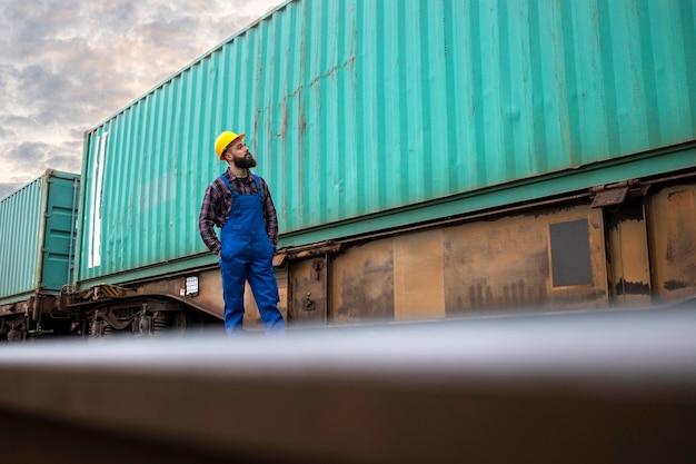 Retrato de trabalhador de transporte verificando contêineres de carga na estação de trem, prontos para serem despachados para o mercado.