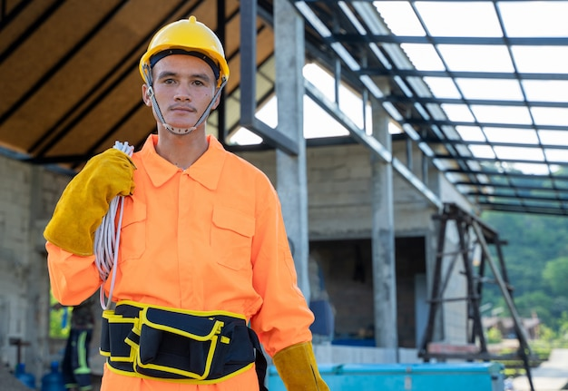 Retrato de trabalhador eletricista com cabo elétrico, preparando-se para a instalação na casa nova