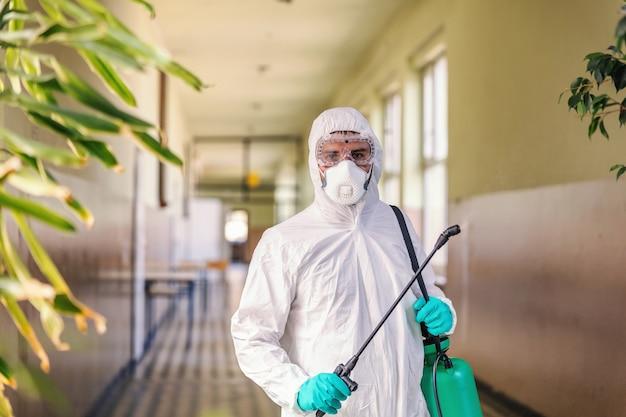 Retrato de trabalhador em uniforme branco estéril, com máscara facial e luvas de borracha em pé no corredor na escola e segurando o pulverizador com desinfetante.
