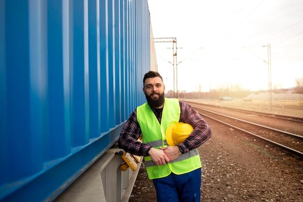 Retrato de trabalhador ferroviário em pé perto do reboque do trem com contêineres na estação.