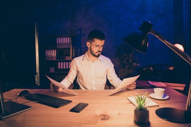 Retrato de trabalhador focado sentado na mesa e olhando documentos
