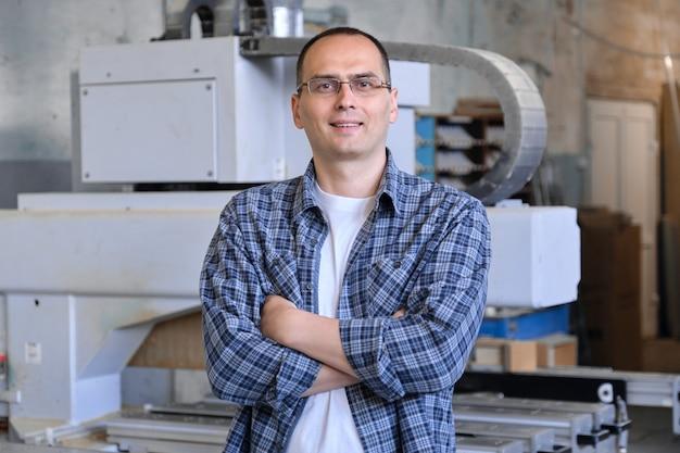 Retrato de trabalhador industrial, homem com os braços cruzados na oficina de carpintaria