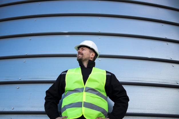 Retrato de trabalhador industrial parado perto de um prédio industrial de metal