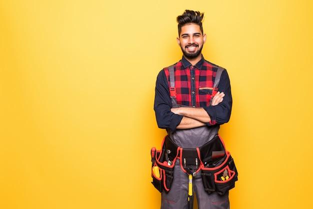 Retrato de trabalhador manual feliz indiano com cinto de ferramentas isolado em espaço amarelo
