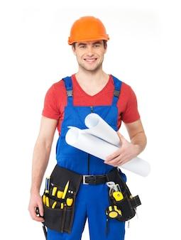 Retrato de trabalhador manual sorridente com ferramentas e papel isolado no branco