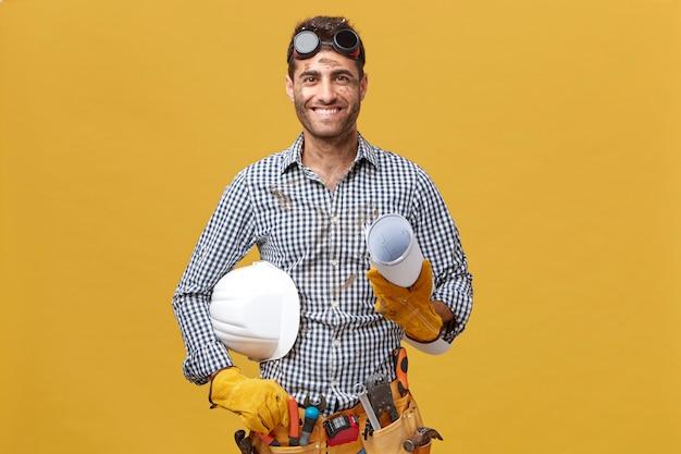 Retrato de trabalhador masculino feliz em roupas casuais, usando óculos de proteção, luvas e tendo o cinto de ferramentas na cintura, segurando a planta e o capacete, tendo um sorriso agradável, regozijando-se com seu sucesso no trabalho