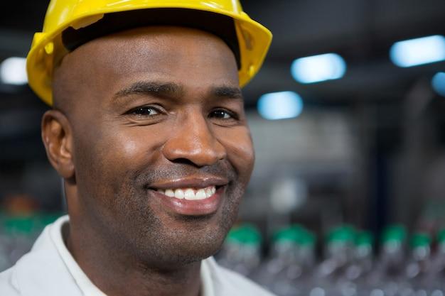 Retrato de trabalhador masculino sorridente usando capacete em armazém