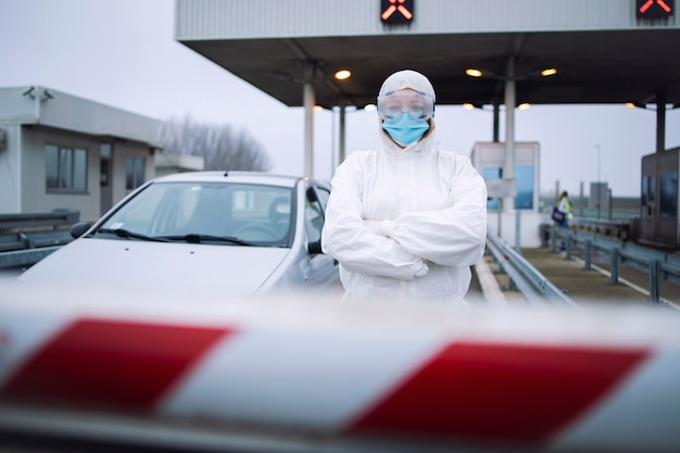 Retrato de trabalhador médico de saúde em traje protetor branco em pé no posto de controle de passagem de fronteira para realizar o teste de pcr em passageiros devido à pandemia do vírus corona.