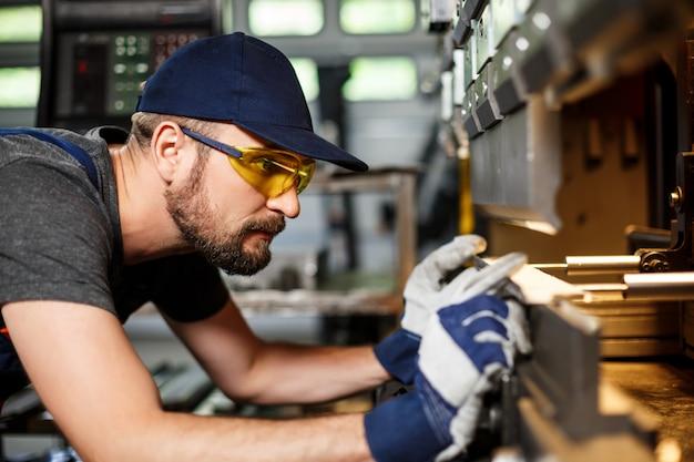 Retrato de trabalhador perto de máquina para metais