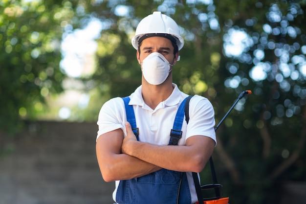 Retrato de trabalhador pesticida confiante com os braços cruzados
