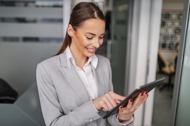 Retrato de trabalhadora positiva caucasiana jovem empresária em pé dentro da empresa corporativa e usando o tablet para ler um e-mail.