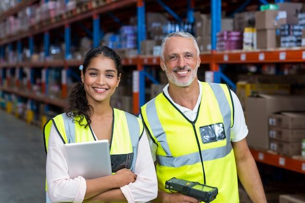 Retrato de trabalhadores de armazém em pé com tablet digital e scanner de código de barras