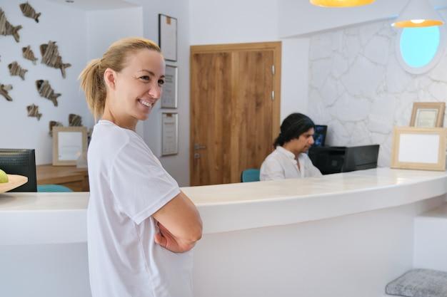 Retrato de trabalhadores de hotel spa, homem e mulher perto da recepção