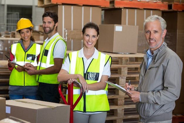 Retrato de trabalhadores e gerente estão sorrindo e posando para a câmera
