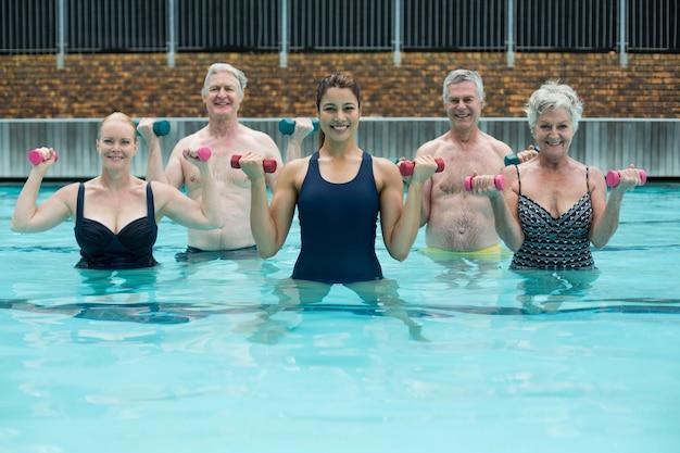 Retrato de treinador e nadadores sênior fazendo halterofilismo em piscina
