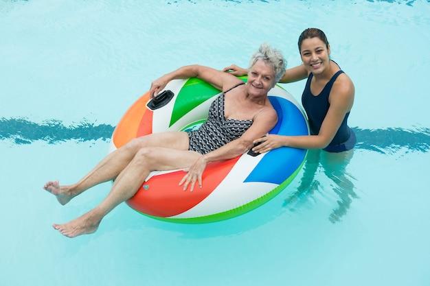 Retrato de treinadora e mulher sênior sorrindo na piscina