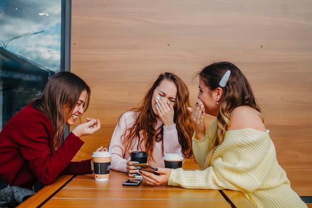 Retrato de três amigas rindo em um café por uma xícara de café