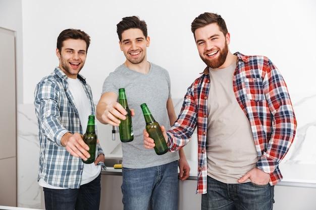 Retrato de três amigos alegres do sexo masculino brindando com shile de garrafas de cerveja dentro de casa