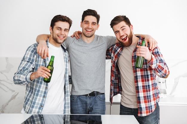 Retrato de três amigos alegres do sexo masculino comemorando em pé com garrafas de cerveja dentro de casa