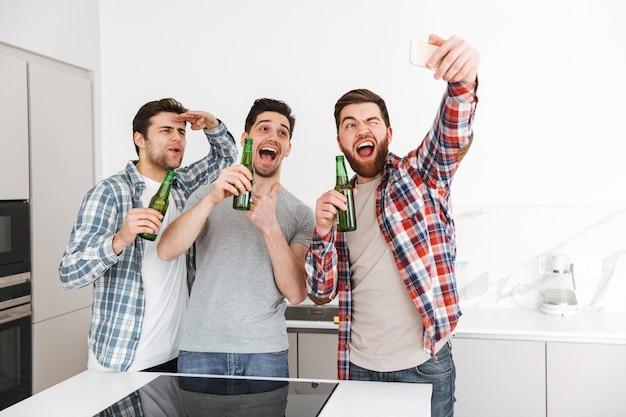 Retrato de três amigos animados do sexo masculino comemorando em pé com garrafas de cerveja e tirando uma selfie dentro de casa