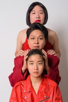Retrato de três amigos asiáticos com diversidade de idade e personalidades juntos contra uma parede branca