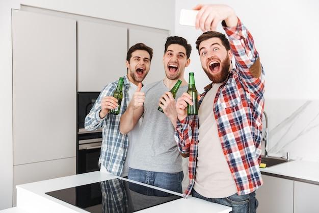 Retrato de três amigos felizes do sexo masculino, comemorando em pé com garrafas de cerveja e tirando uma selfie dentro de casa